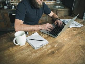 : Mann sitzt zuhause an seinem Schreibtisch